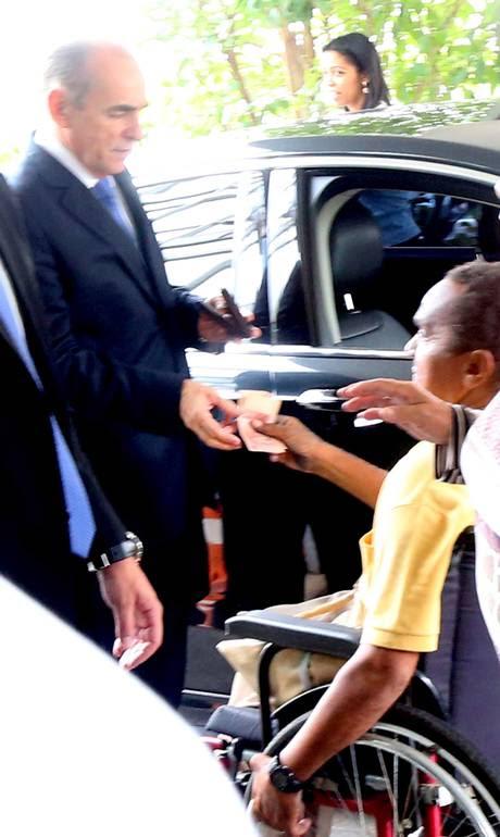 O ministro Marcelo Castro dá R$ 40 reais ao cadeirante Marcilio Pereira Silva Neto na porta do Ministério da Saúde - Ailton de Freitas / Agência O Globo