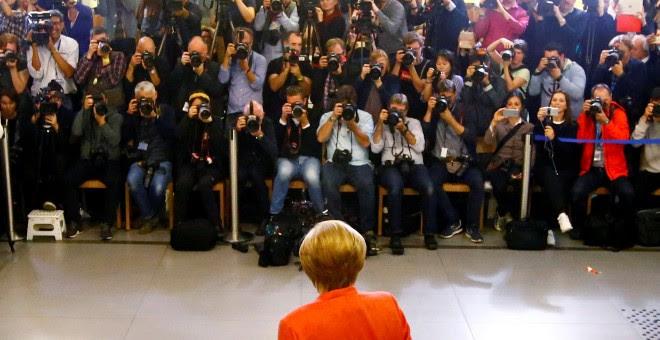 La canciller alemana, Angela Merkel, deposita su voto ante una nube de fotógrafos. REUTERS/Fabrizio Bensch