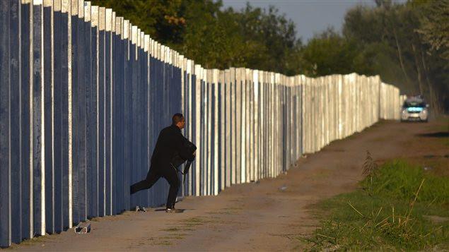 Un migrant franchit la clôture hongroise, lundi, devant une voiture de la police nationale.