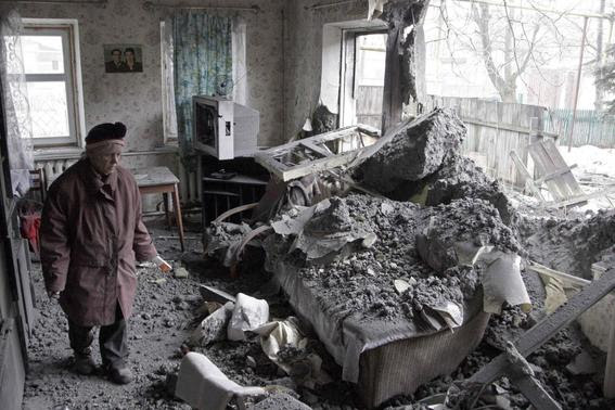 A woman surveys damage done to a house, which according to locals was recently damaged by shelling, in the suburbs of Donetsk January 30, 2015.  REUTERS-Alexander Ermochenko