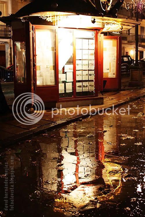 Fotografía de un quiosco-inmobiliaria produciendo fantásticos reflejos en una noche lluviosa de Baeza, Jaén