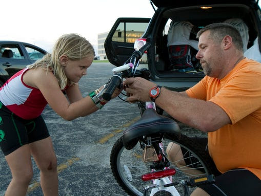 Molly Flynn, 7, works on putting a cowbell onto her
