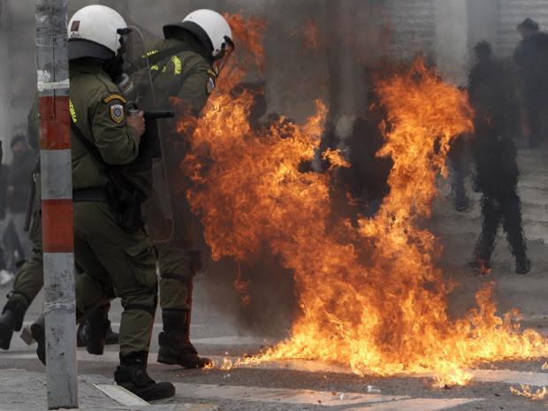 Policias tentam escapar das chamas depois que uma bomba foi atirada em frente ao Parlamento em Atenas, nesta quarta-feira (23). (Foto: Reuters)