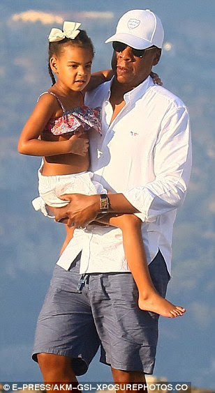 Doting dad: Her husband, meanwhile, opted for yacht-set staple, and teamed an open-neck white shirt with pale slate shorts and a pair of brilliant white trainer