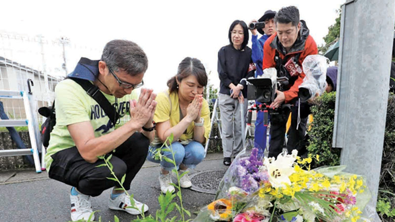 A man prays next to flowers and tributes laid at the scene where over 30 people died in a fire at an animation company building in Kyoto yesterday. - AFP