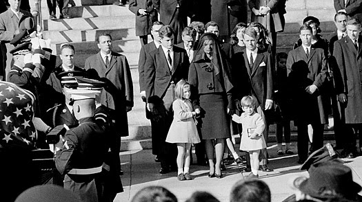 president kennedy death. The Kennedy family stands