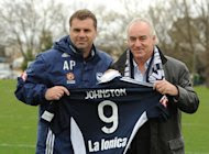 Melbourne Victory coach Ange Postecoglou (L) presents Liverpool football legend Craig Johnston a Victory playing shirt after a team training session in Melbourne on July 23, 2013