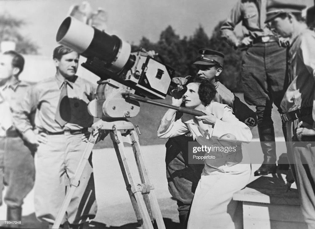 Circa 1930's, Germany, German film director Leni Riefenstahl looks through the lens of a film camera while being watched by uniformed Nazi officials