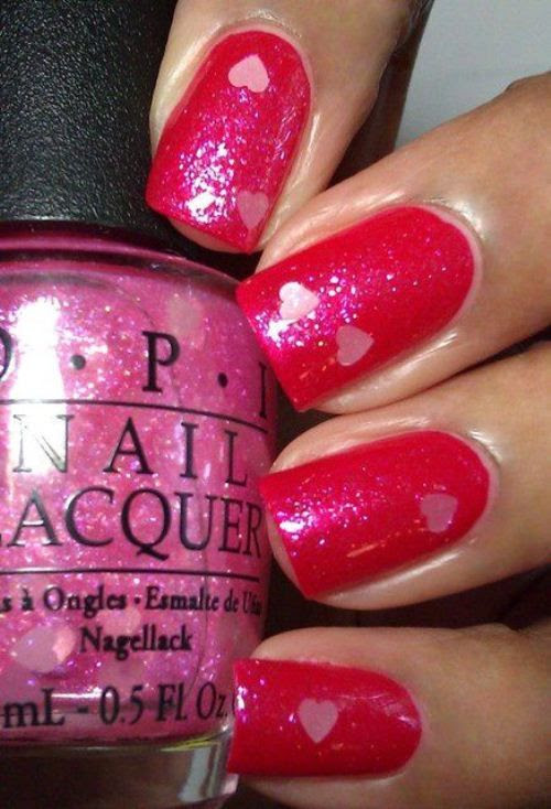 Draw some hearts on your nails with red nail polish for the base coat and pink nail polish for the little hearts..