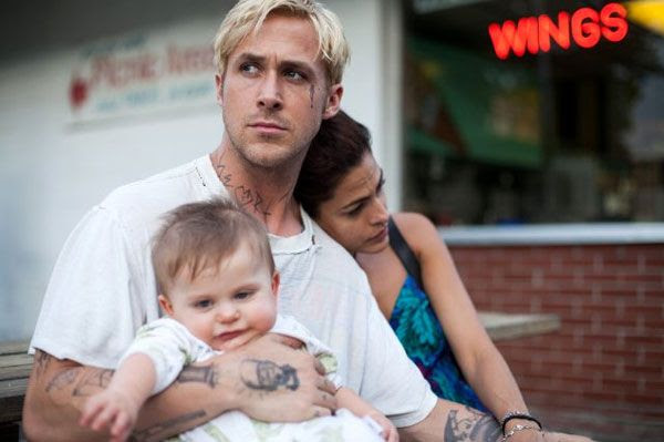 Luke (Ryan Gosling) resorts to committing bank robberies to support his infant son, along with Romina (Eva Mendes) in THE PLACE BEYOND THE PINES.