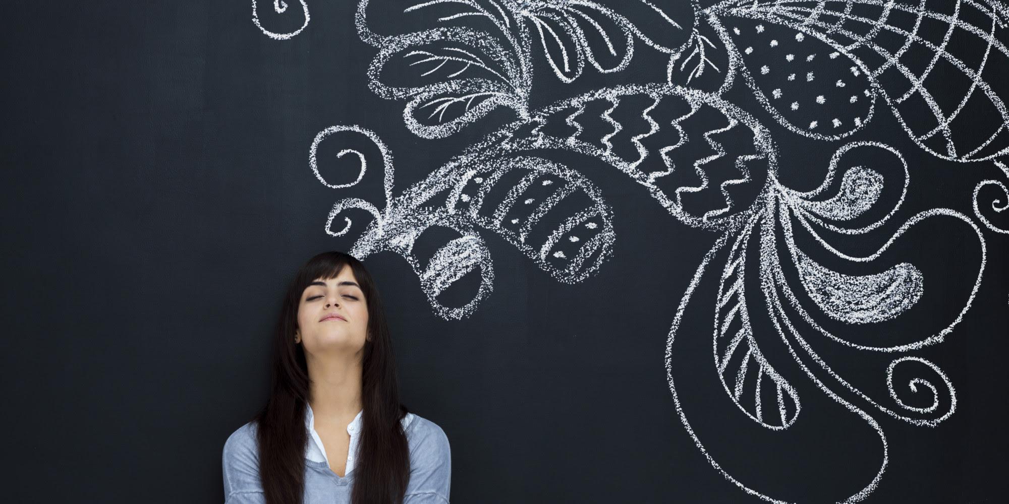 FOTO: Mulher com os olhos fechados, encostada num quadro negro, onde existem desenhos abstratos desenhados com giz branco, como se estivessem saindo de sua cabeça