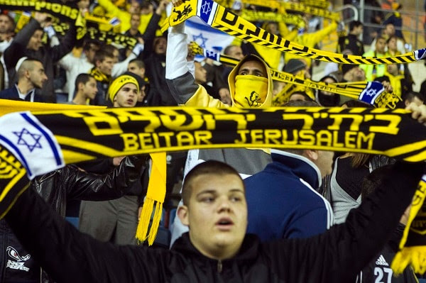 Fans of Beitar Jerusalem shout slogans during a match against Bnei Sakhnin as part of the Israeli Premier League, at Teddy Stadium in Jerusalem February 10, 2013. (REUTERS/Nir Elias)