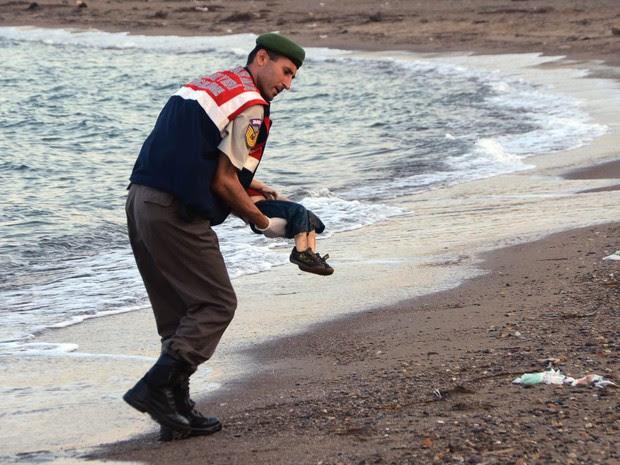 Policial paramilitar recolhe o corpo de uma criança morta que apareceu em praia da ilha de Kos, na Grécia. Vários migrantes morreram afogados e alguns seguem desaparecidos após botes lotados naufragarem durante tentativa de chegar ao território grego (Foto: AP/DHA)