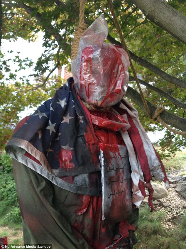 The most intense part of the gruesome display is what appears to be a US soldier, wrapped in an American flag, hanging from the front tree with a plastic bag around the head