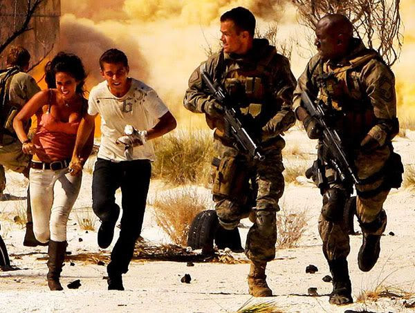 A close-up of Sam, Mikaela, Captain Lennox and Sergeant Epps running for cover.