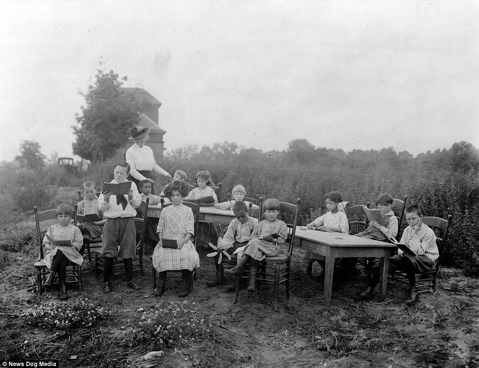In a bid to stamp out the disease, children were taught outdoors all day every day and lessons were never abandoned no matter how cold it got. School children are pictured seated at two tables outdoors in an open air school in Cincinnati, Ohio, circa 1912