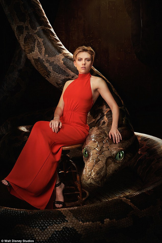 Lady in red: Scarlett was captivating in a floor-length, halterneck red gown, as she rested one hand on the head of a massive python, which represents her 'alluring, coquettish' character Kaa