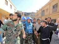 A handout picture released by Shaam News Network shows Abdul Razzaq Tlas (L) leader of the opposition Katibat al-Faruq, guides Moroccan UN observer, Colonel Ahmed Himmiche during the monitor's visit to the restive city of Homs. (AFP Photo/)