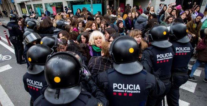 Efectivos de los Mossos d'Esquadra desalojan a un grupo de mujeres que cortaban la Gran Via de Barcelona.- EFE
