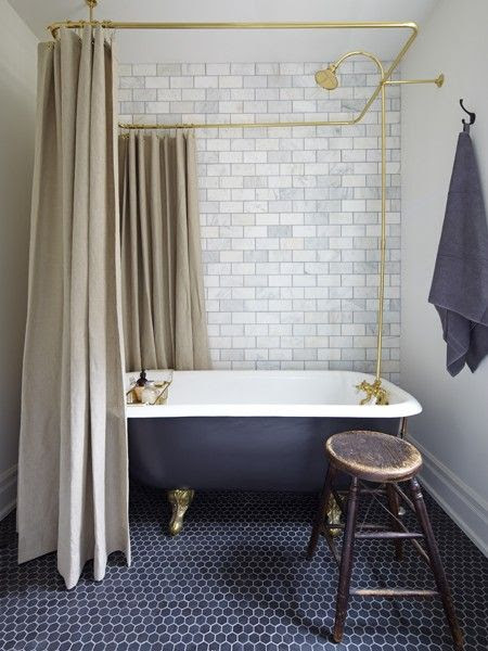 Absolutely love the bath and hexagonal tiled blue floor, the brick feature on the back wall and beige shower curtains work so well together