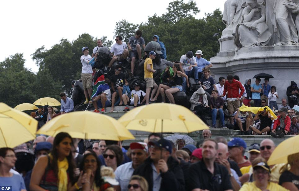 The rain won't dampen our spirits! Spectators embraced the wet weather and sheltered themselves with umbrellas and coats as rain started to fall in the capital
