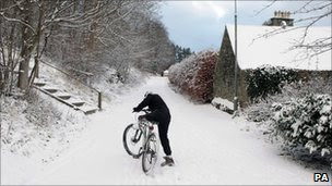 Man on bicycle in snow in Peebles, Scottish Borders