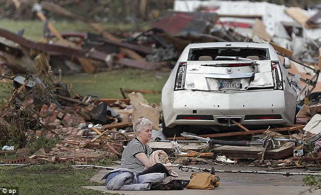 Sadness: A woman holds her cat as she sits in the driveway of her demolished home