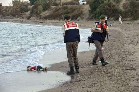 Policiais turcos fotografam o corpo do sírio Aylan Kurdi, de três anos, que morreu afogado após o naufrágio de uma embarcação de refugiados