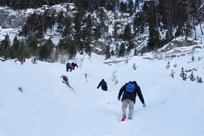 Los migrantes caminan por la nieve en un barranco empinado