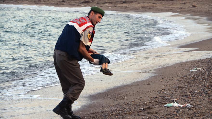 Un oficial de la policía paramilitar lleva el cuerpo sin vida de un niño refugiado después de que el barco en el que viajaba volcase junto a diezpersonas máscerca de la isla griega de Kos./ AP PhotoDHA