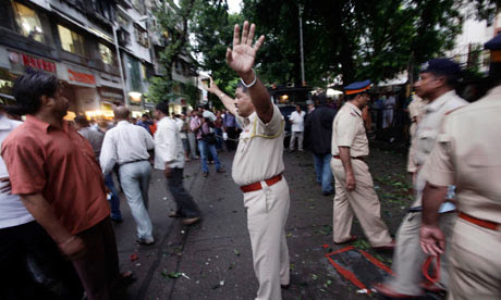 A policeman controls the crowd at the site of an explosion at Dadar in Mumbai, India
