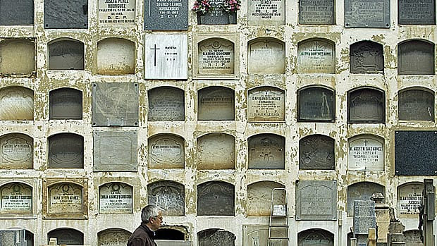 A man stands in front of rows of tombs in a Madrid cemetery that's threatening to evict thousands of burial whose leases are up.