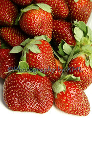 pile of red ripe strawberries on a white background