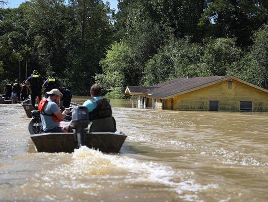Boats pass a home partially submerged by floodwaters