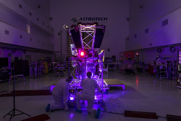 Parker Solar Probe team engineers use a laser to illuminate the cells on the twin solar arrays installed aboard the spacecraft on May 31, 2018...at Astrotech Space Operations in Titusville, Florida.