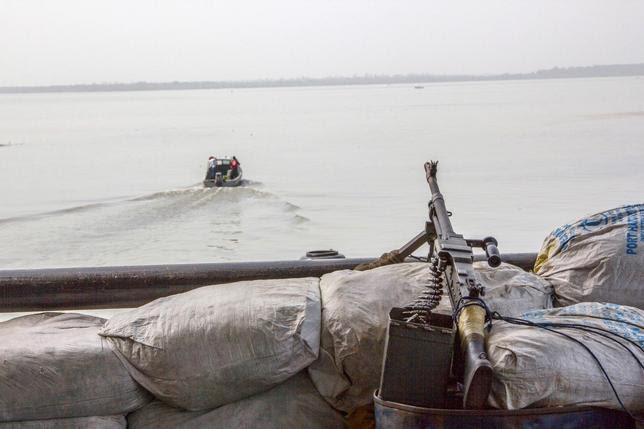 A machine gun is seen on a sandbag on a boat off the Atlantic coast in Nigeria's Bayelsa state December 19, 2013.