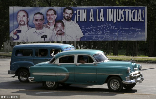 Cars drive past an 'End to Injustice!' banner featuring five Cuban prisoners held in U.S. custody, two of whom were previously released, in Havana December 17, 2014. The aging automobiles are a sign of Cuba's international isolation, as 50-year-old cars are commonplace on the streets of Havana