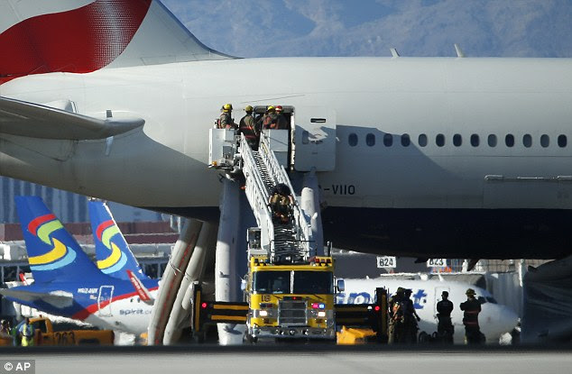 Firefighters stand atop a ladder next to the doors of the plane that caught fire