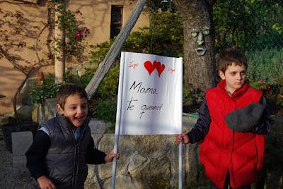 Iago y Diego sujetando una pancarta que dice, mama te queremos