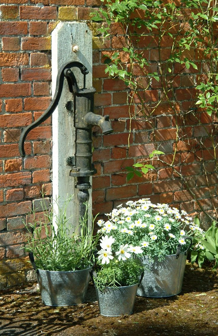 Old hand pump by three galvanized planters