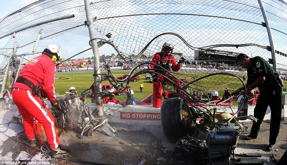 Aftermath: Safety staff attend to the injured fans who were sent into panic as the collision unfolded in front of them before some cars breached the fencing