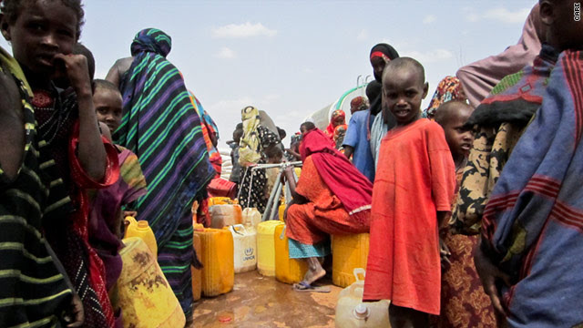 Malnourished children wait for aid at the Dadaab refugee complex in Kenya as women collect water from a CARE pump.
