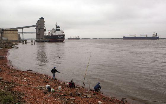 Rosario: Al fondo, los barcos cargan cereales; abajo, pescadores pobres