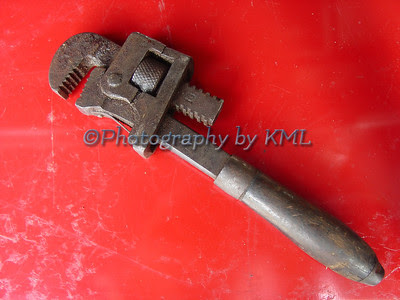 an old antique wrench against a red background