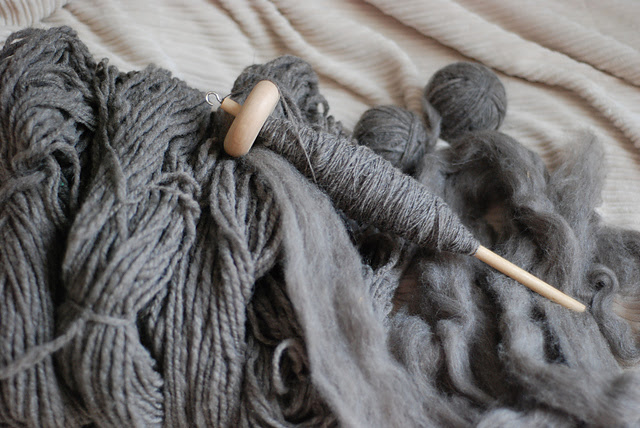 Spinning work in progress spindle-spinning a sweater from natural grey wool