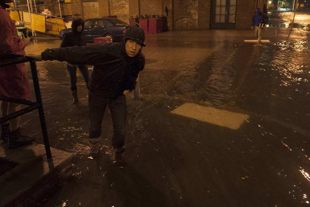 A man looks down a flooded street in the Down Under the Manhattan Bridge Overpass (DUMBO) neighborhood of Brooklyn in New York. Hurricane Sandy could be the biggest storm to hit the United States mainland when it comes ashore on Monday night, bringing strong winds and dangerous flooding to the East Coast from the mid-Atlantic states to New England, forecasters said on Sunday.