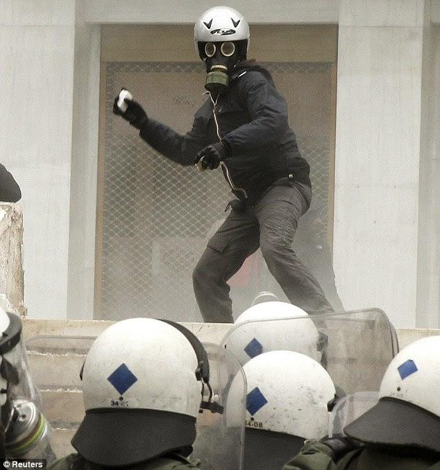 Απειλητικός: Ένας διαδηλωτής, φορώντας μια μάσκα και κράνος του φυσικού αερίου, εκσφενδονίζει πέτρες σε αξιωματικούς κατά τη διάρκεια συγκρούσεων στο Σύνταγμα της πρωτεύουσας στην πλατεία