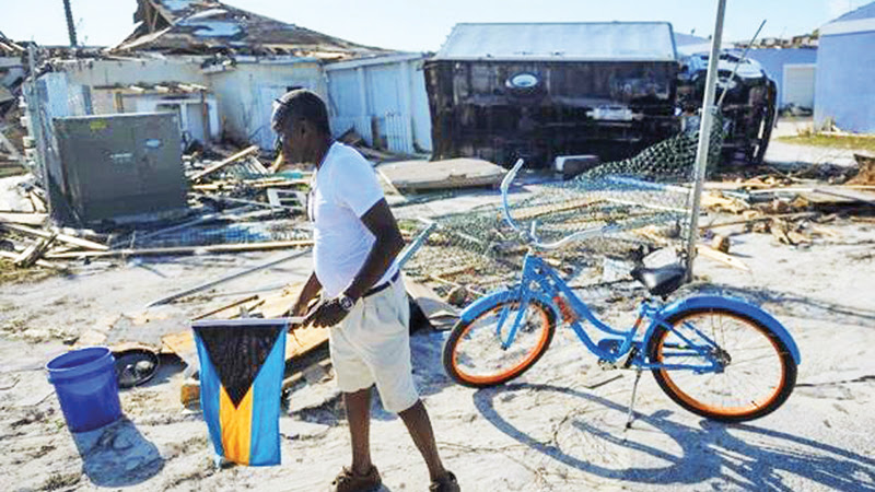 A man carries the Bahamian flag as he walks past a damaged truck on Treasure Cay in the hurricane-hit Bahamas.