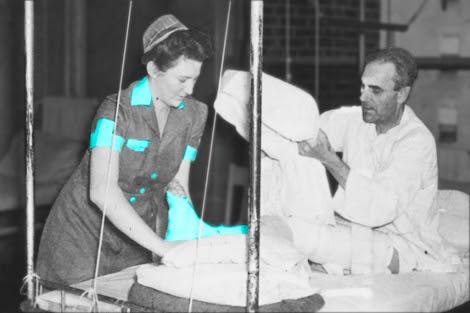 Una enfermera atiende a un paciente en una imagen en blanco y negro