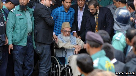 Ghulam Azam is escorted by security personnel and lawyers as he emerges from the Bangladesh International Crimes Tribunal in Dhaka on January 11, 2012